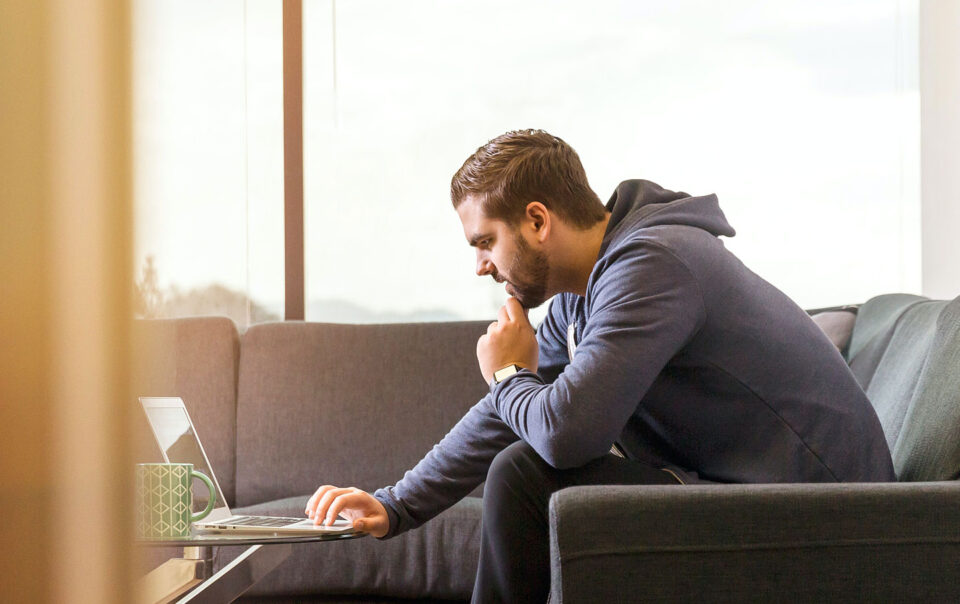 Man sitting on couch looking at his laptop computer.
