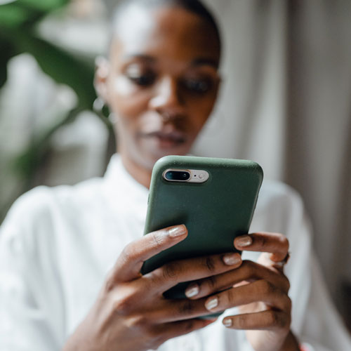Woman completing electronic transfer on mobile device