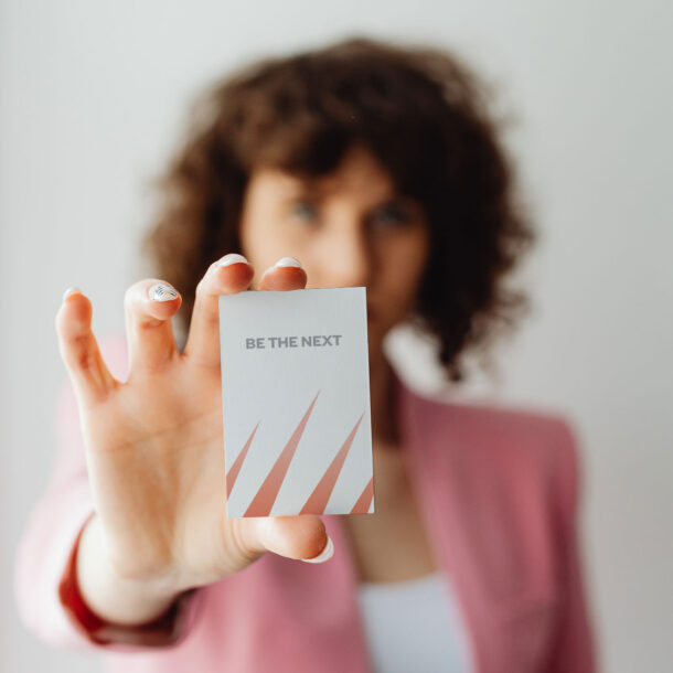 """Woman holding a business card with the words """"BE THE NEXT"""" on it."""
