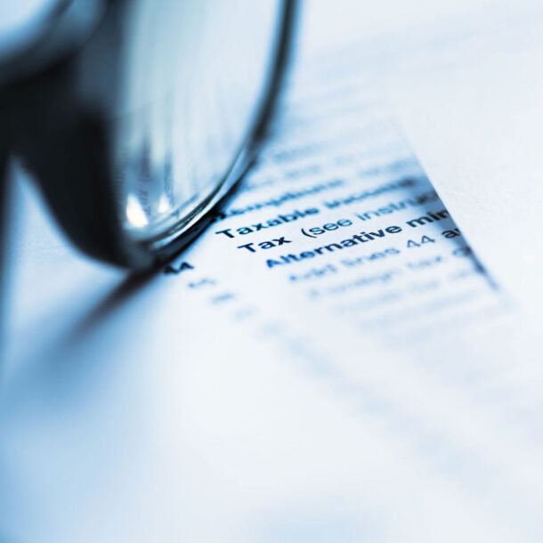 Document with the Word Tax on it with a pair of eyeglasses on top of it.