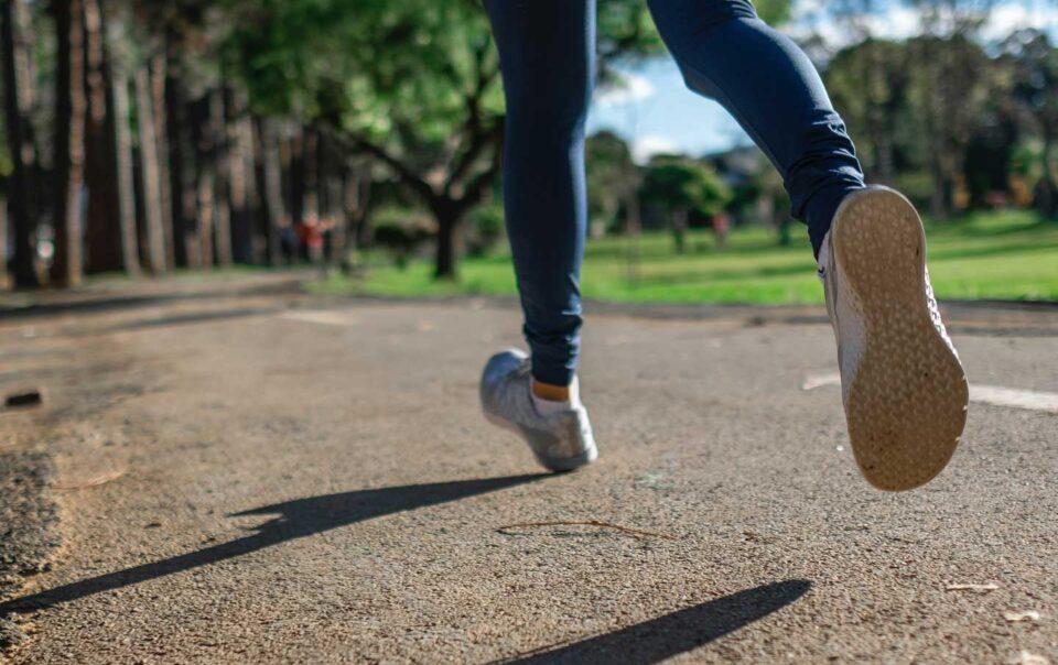 Woman running along park path.