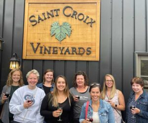 Group shot of employees in front of the Saint Croix Vineyard sign.