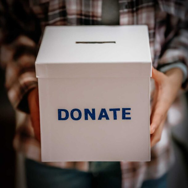Close up of woman holding a donation box.